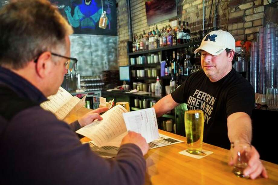 Whichcraft Taproom General Manager Nick Alfano, right, serves drinks to Scott Ringlein, left, and Melissa Ringlein (not pictured) Monday afternoon in downtown Midland. (Katy Kildee/kkildee@mdn.net)