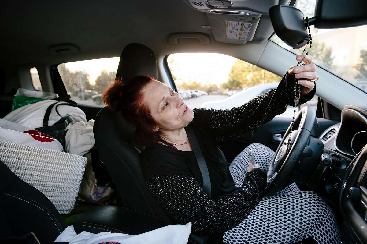 While sitting in her car where she spent the night in a parking lot of a Kohl's store, Lori Angel touches a rosary hanging form her rearview mirror while talking about having to evacuate from her home in Santa Rosa, in Petaluma, California, on Monday, Oct. 28, 2019.
