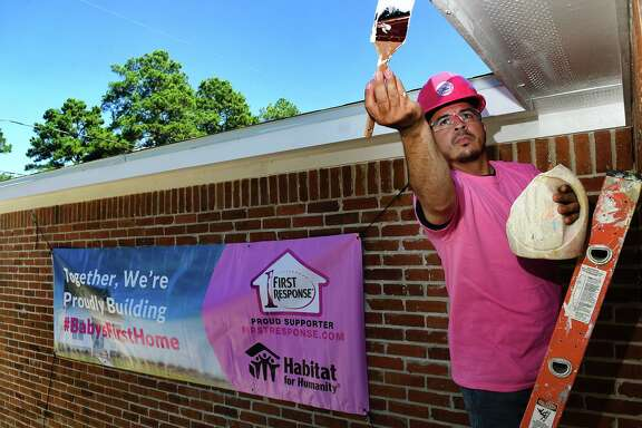 Juan Casa works on the trim of his family's new home being built as part of the pay-it-forward program with First Response in their partnership with Habitat for Humanity to help build safe and affordable homes for needy families in Tomball on Oct. 22, 2019.