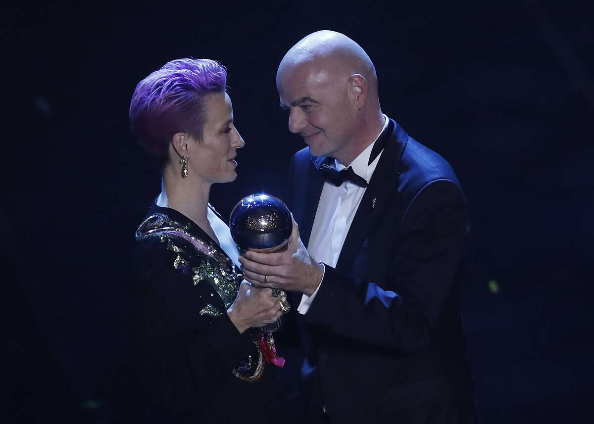 FILE - In this Sept. 23, 2019, file photo, U.S. forward Megan Rapinoe, left, receives the Best FIFA Women's player award from FIFA president Gianni Infantino during the ceremony of the Best FIFA Football Awards in Milan's La Scala theater, northern Italy. Rapinoe is enjoying the whirlwind of a two-time World Cup winner. She picked up the FIFA Player of the Year award in Milan rocking a deeper shade of lavender hair, sent off retiring U.S. coach Jill Ellis with an undefeated victory tour and kept up the fight for pay equity against the U.S. Soccer Federation. (AP Photo/Antonio Calanni, File)