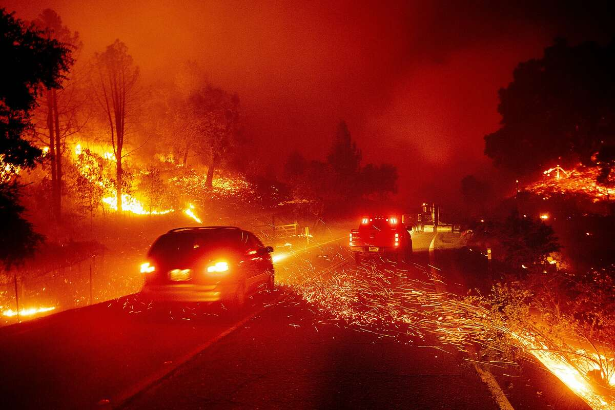 Embers fly across a roadway as the Kincade Fire burns through the Jimtown community of Sonoma County, Calif., Oct. 24, 2019.