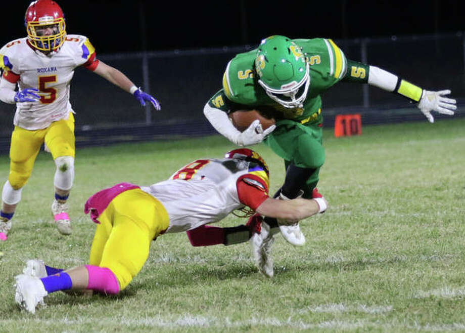 Roxana's Braeden Wells (left) shoots in to take Southwestern running back Gavin Day down for a loss in the first quarter of Friday night's SCC football game at Knapp Field in Piasa. Photo: Greg Shashack | The Telegraph
