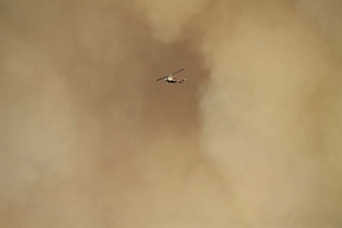 A Cal Fire helicopter flies past a smoke cloud from the Kincade Fire in Geyserville on Friday, Oct. 25, 2019.