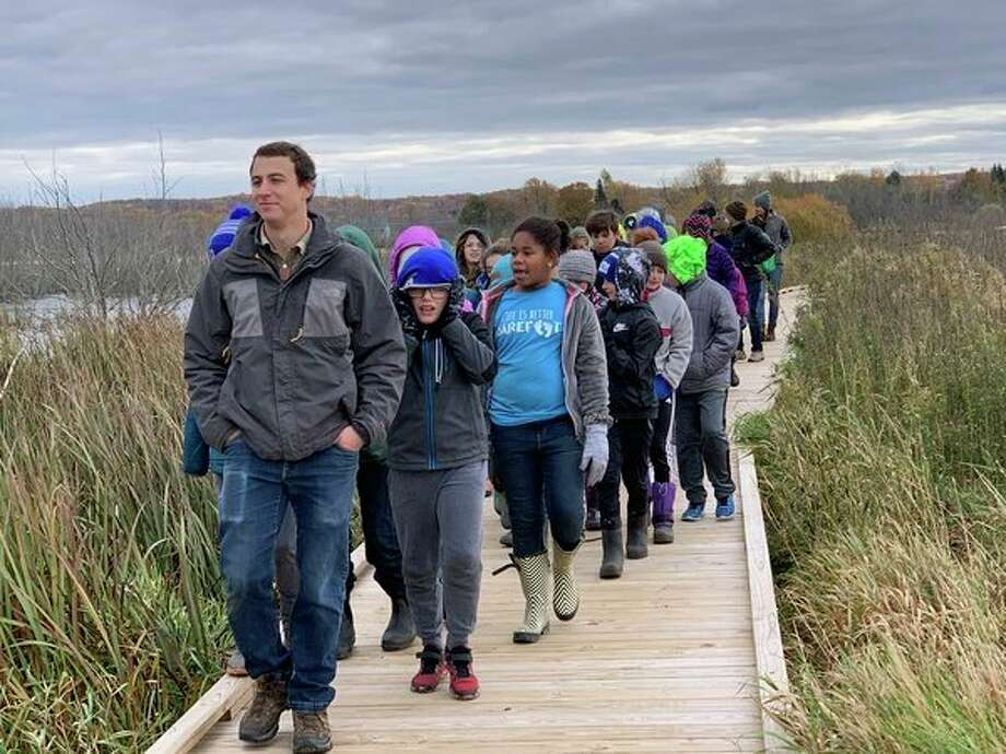 John, a member of the Grand Traverse Regional Land Conservancy, points out design features and wildlife to students on the Arcadia Marsh boardwalk. (Courtesy photo)