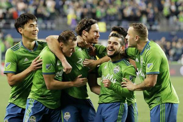 Seattle Sounders midfielder Gustav Svensson, center, celebrates with teammates after he scored a goal against Real Salt Lake during the second half of an MLS Western Conference semifinal playoff soccer match Wednesday, Oct. 23, 2019, in Seattle. The Sounders won 2-0.