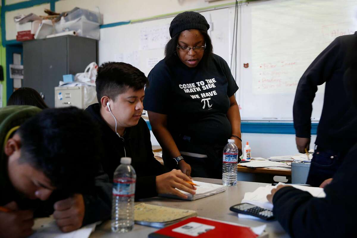 Mission High School math teacher Kimberly Rosario (right) discusses classwork with sophomore Jason Perez (left) as she teaches Geometry class at Mission High School on Monday, October 28, 2019 in San Francisco, Calif.