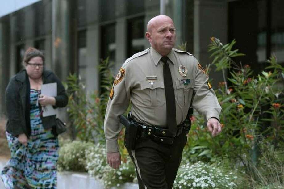 """In this Oct. 24, 2019 file photo, St. Louis County police Sgt. Keith Wildhaber returns from lunch break to the St. Louis County courthouse on the third day of his discrimination case against the county in Clayton, Mo. Some St. Louis County leaders are calling for a police leadership shakeup after a jury found that Wildhaber was discriminated against because he's gay and recommended that he be awarded nearly $20 million. Councilwoman Lisa Clancy says Police Chief Jon Belmar should resign because of what she described as a """"culture of rampant racism and homophobia."""" (Cristina M. Fletes/St. Louis Post-Dispatch via AP, File)"""