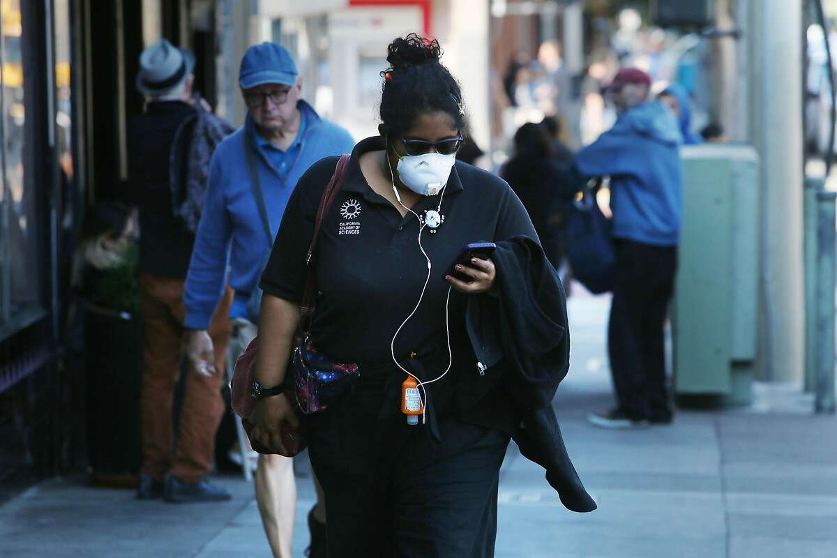 Kristina Lee, who has athsma, wears a N-95 mask as she walks on Ninth Avenue on Monday, October 28, 2019 in San Francisco, Calif. Lee says in the past poor air quality days after fires that she she suffered from light headedness and because she is at risk and recently her athsma had been acting up, is taking the extra precaution of wearing the mask.
