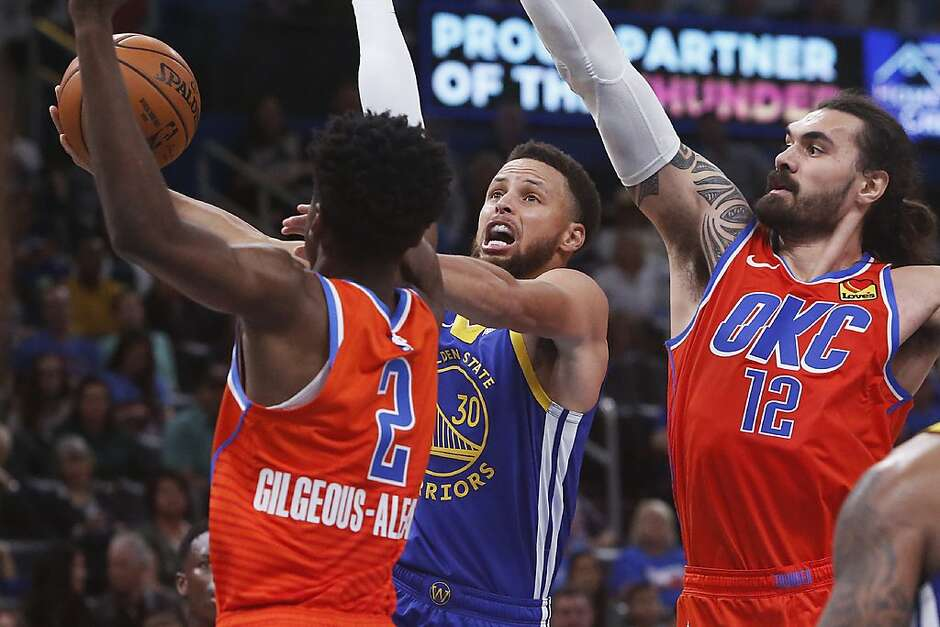 Golden State Warriors guard Stephen Curry (30) goes to the basket between Oklahoma City Thunder guard Shai Gilgeous-Alexander (2) and center Steven Adams (12) in the first half of an NBA basketball game Sunday, Oct. 27, 2019, in Oklahoma City. (AP Photo/Sue Ogrocki)