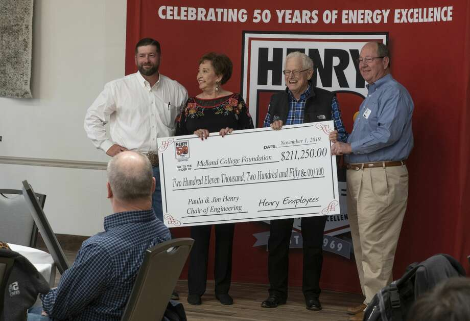 Blake Pitcock and Mike Curry present Paula and Jim Henry a check for an endowment started at Midland College in their name 10/28/19 during the week-long festivities to celebrate Henry Resources 50 years.  Tim Fischer/Reporter-Telegram Photo: Tim Fischer/Midland Reporter-Telegram