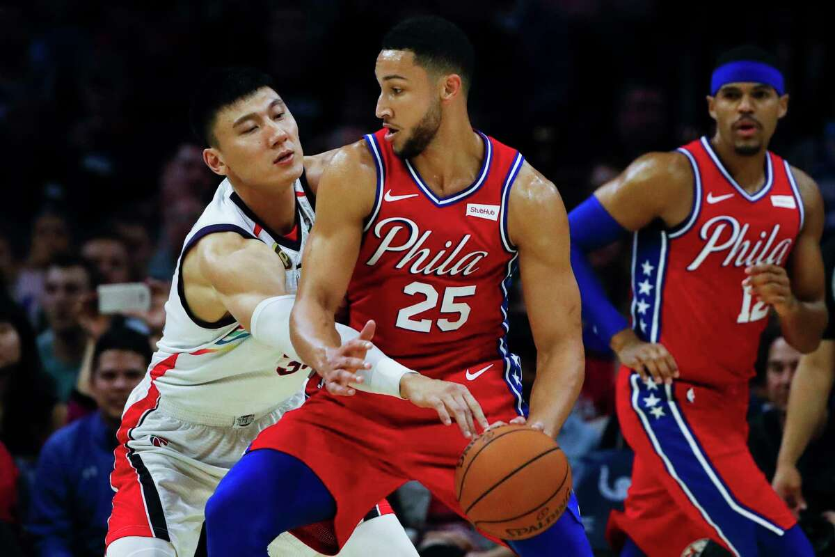 Philadelphia 76ers' Ben Simmons (25) drives to the net as Guangzhou Loong-Lions' Yongpeng Zhang defends and Philadelphia 76ers' Tobias Harris, right, watches during the first half of an NBA exhibition basketball game Tuesday, Oct. 8, 2019, in Philadelphia. (AP Photo/Matt Rourke)