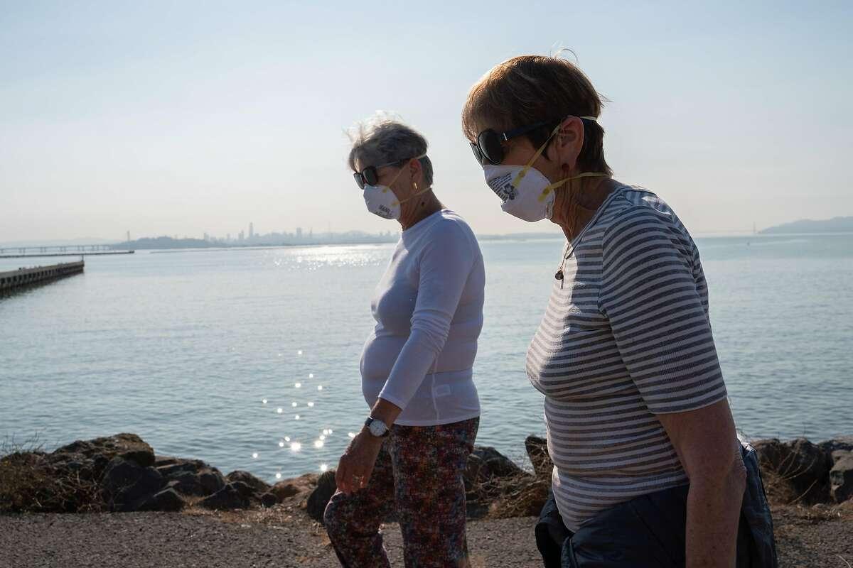 Sara Orem (left) and Phyllis Rothman, both from Berkeley, wear N95 masks during a walk through the marina in Berkeley, Calif. on Monday, Oct. 28, 2019.