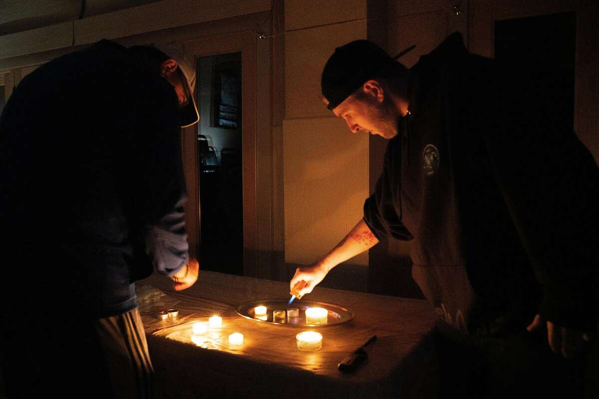 People light candles during a power outage at Zion Lutheran Church in Oakland, Calif. on Monday, Oct. 28, 2019.