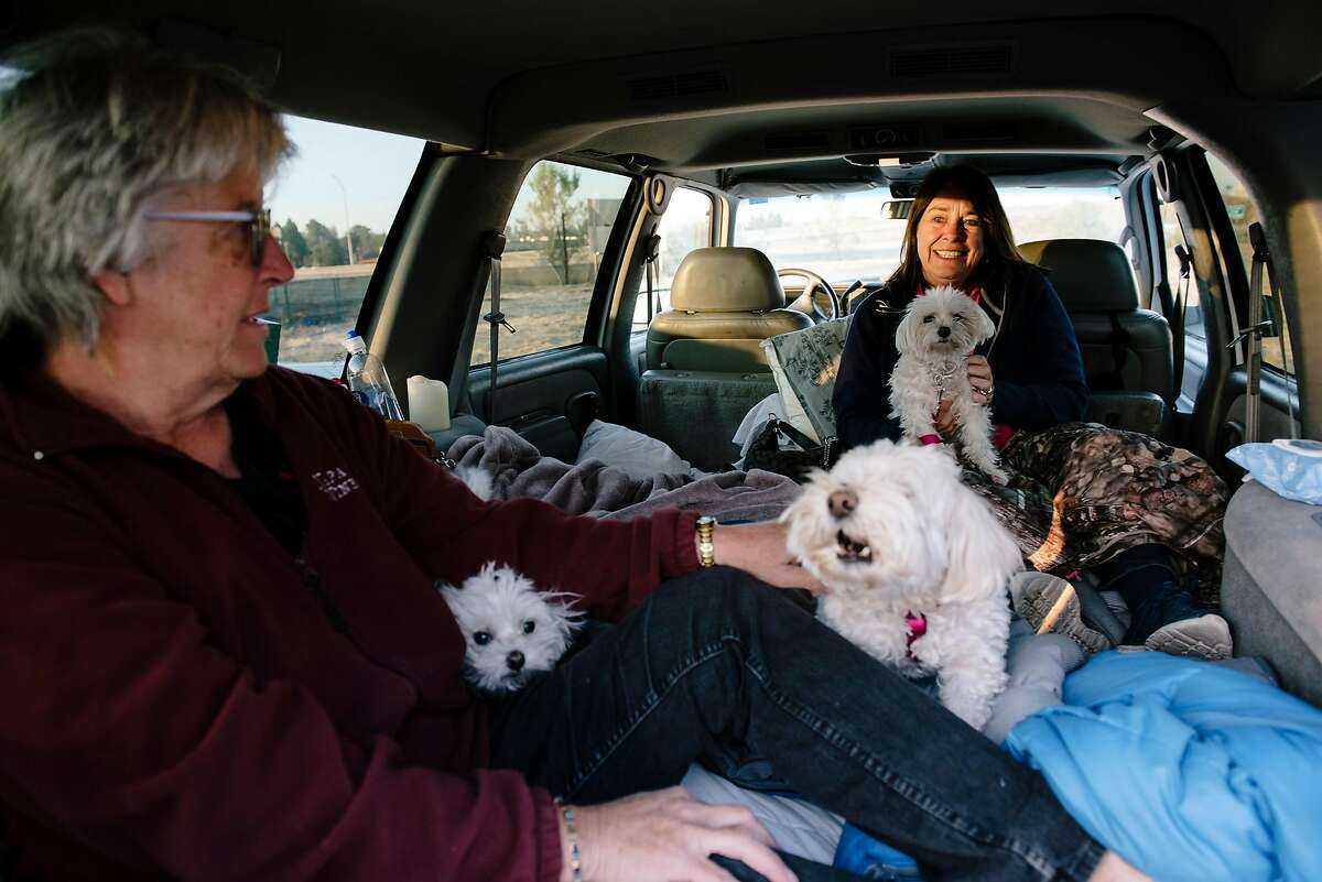 Karen Marley, left, and Nancy Tonelli, who evacuated from nearby Windsor, and their dogs spent the night in the back of their truck in a Kohl's store parking lot in Petaluma, California, on Monday, Oct. 28, 2019.