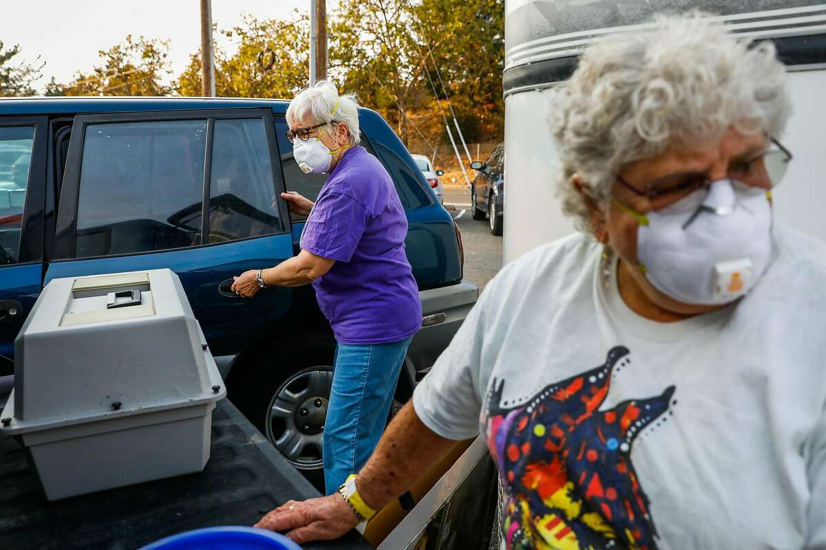 Charlotte Schatz and her wife Susan Godbois (left) pack up their belongings as they head home after days of sleeping in their car due to evacuating the Kincade Fire in Santa Rosa, California, on Monday, Oct. 28, 2019.