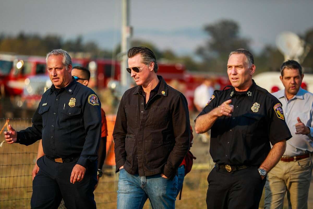 Gov. Gavin Newsom chats with firefighters at the Sonoma County Fairgrounds where people have gone to evacuate from the Kincade fire in Santa Rosa, California, on Monday, Oct. 28, 2019.