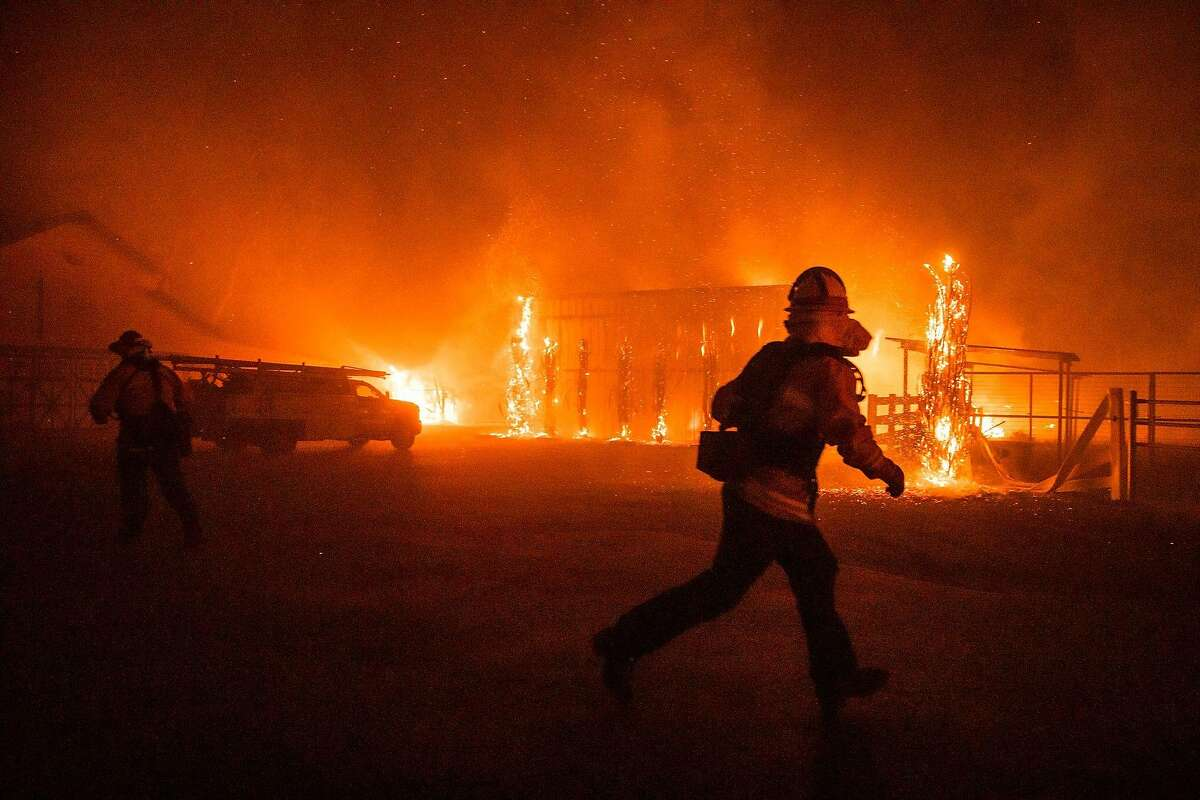Firefighters battle a wind-driven fire burning structures on a farm during the Kincade fire in Windsor, California on October 27, 2019. - California's governor declared a state-wide emergency on October 27 as a huge wind-fueled blaze forced evacuations and massive power blackouts, threatening towns in the famed Sonoma wine region. (Photo by Philip Pacheco / AFP) (Photo by PHILIP PACHECO/AFP via Getty Images)