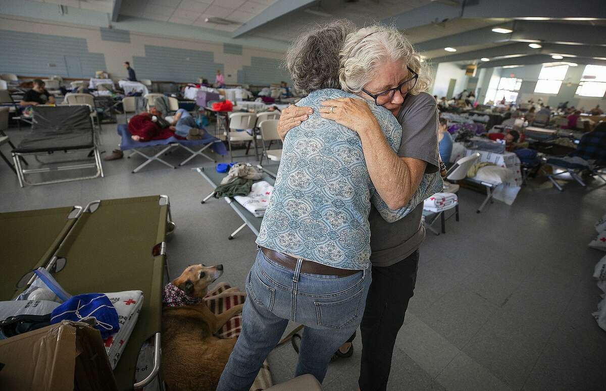 In this Sunday, Oct. 27, 2019, photo, Red Cross volunteer Barbara Wood gives a hug to a Kincade fire evacuee at a Red Cross shelter set up for wildfire evacuees at the Sonoma County Fairgrounds in Santa Rosa, Calif., after evacuating her Santa Rosa home in the morning. The Red Cross established the shelter for evacuees with pets at the Sonoma County Fairgrounds. (John Burgess/The Press Democrat via AP)