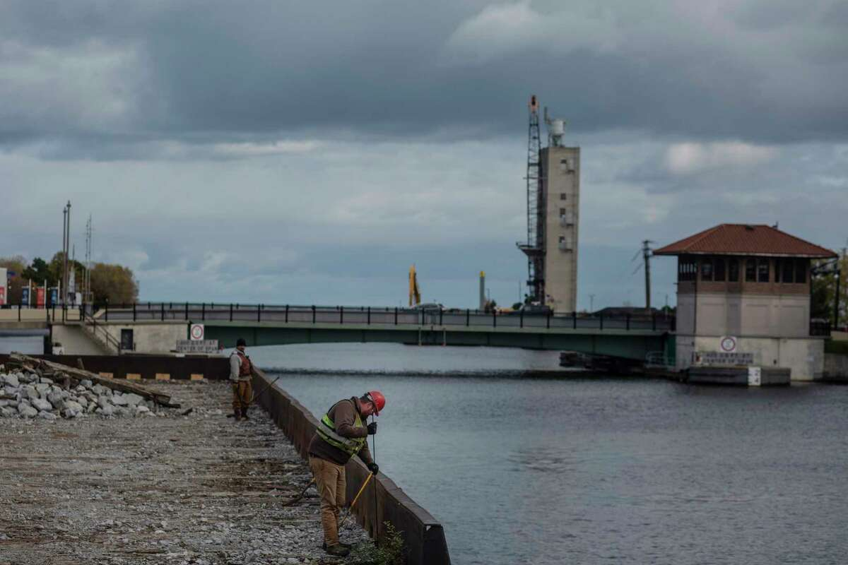 Construction workers work on a barge on the Manitowoc River.