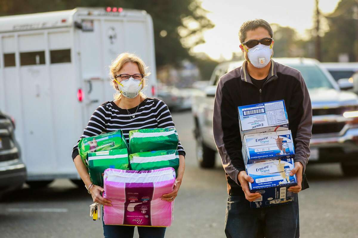 Sonya Wanhala and Mike Weiner (right) wear masks as they donate supplies to the Red Cross following the Kincade Fire in Santa Rosa, California, on Monday, Oct. 28, 2019.
