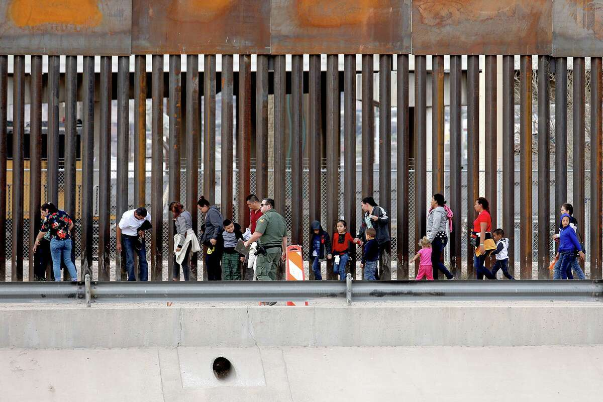 In this March photo, migrants seeking asylum turn themselves in to U.S. Border Patrol agents in El Paso.