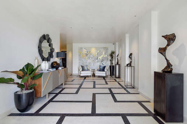 French limestone and Petit Belgian granite arranged according to the Golden Ratio lines a stately foyer with gallery walls and recessed lighting.