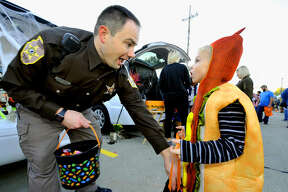 Dressed as a hotdog, Henry Godwin, 6, of Edwardsville, gets candy from Dep. Drew Beckley of the Madison County Sheriff's Office during the department's Trunk-or-Treat event Sunday in Edwardsville. The event was originally scheduled for Saturday, but moved to Sunday due to heavy rains in the Edwardsville area.