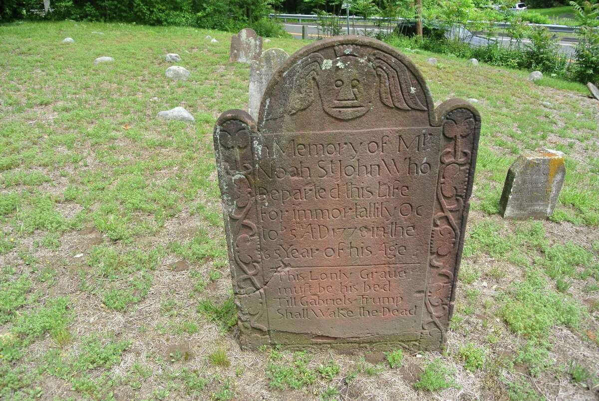 A stone marks the resting place of Noah St. John at the Sharp Hill Cemetery in Wilton, Conn.
