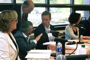 Connecticut Gov. Ned Lamont, center, speaks with Senate Republican Leader Len Fasano, second from left lower, and Democratic Senate President Pro Tempore Martin Looney, second from left standing, about how to handle a vote by the new board of directors overseeing public-private Partnership for Connecticut on Friday, Oct. 18, 2019 in New Haven, Conn. The new nonprofit, which is overseeing an initiative to help high school students in struggling school districts succeed, met publicly for the first time. (AP Photo/Susan Haigh)