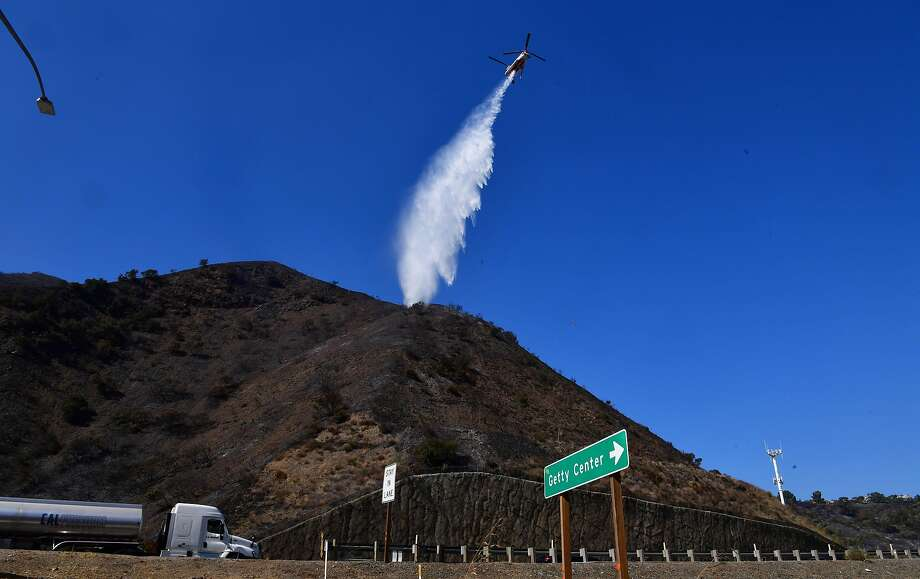 A helicopter makes a water drop over hillsides near the renowned Getty Center in Los Angeles on Tuesday. Photo: Frederic J. Brown / AFP Via Getty Images