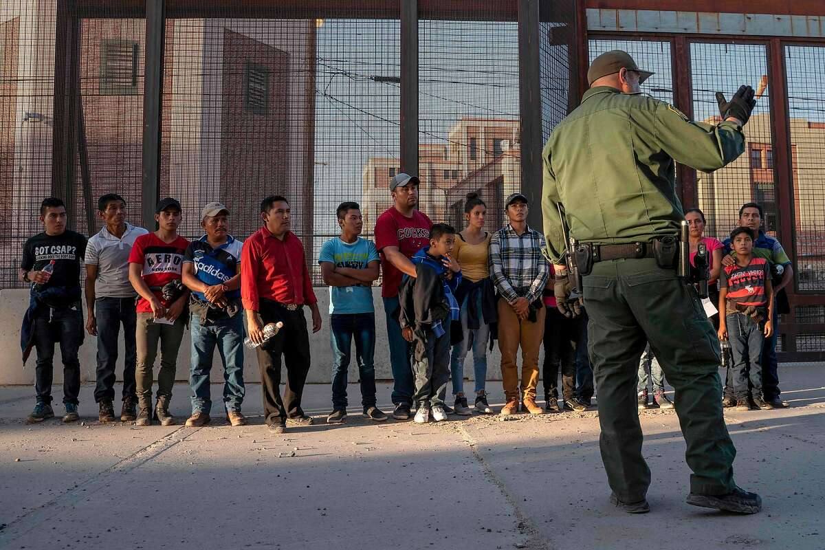 (FILES) In this file photo taken on May 16, 2019 migrants, mostly from Central America, que to board a van which will take them to a processing center, in El Paso, Texas. - The US government plans to collect the DNA of all migrants detained after entering the country illegally, officials said on October 2, 2019. The Department of Homeland Security (DHS) is developing a plan to take DNA samples from each of the undocumented immigrants and store it in a national database for criminal DNA profiles, they said. (Photo by Paul Ratje / AFP) (Photo by PAUL RATJE/AFP via Getty Images)