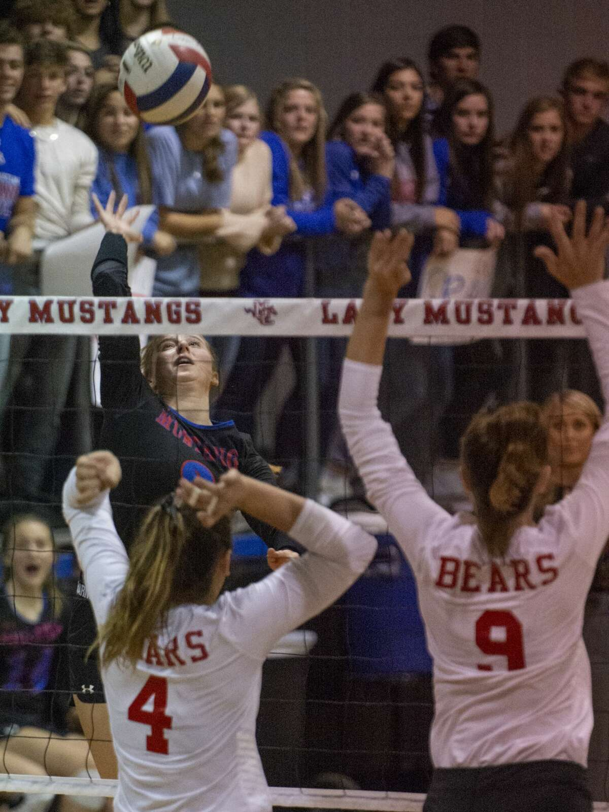 Midland Christian's Avery Jauz goes up for a kill as Ursuline Academy's Kayliegh Currier and Lexi Lewis go up to block 10/29/19 at the McGraw Event Center. Tim Fischer/Reporter-Telegram