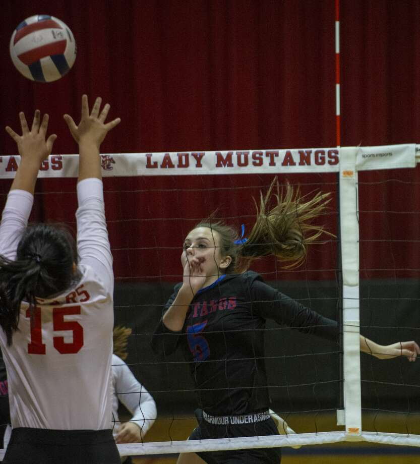 Midland Christian's Cali Joy Copeland tips the ball over the reach of Ursuline Academy's Mia McCord 10/29/19 at the McGraw Event Center. Tim Fischer/Reporter-Telegram Photo: Tim Fischer/Midland Reporter-Telegram