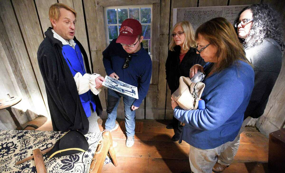 """Tom Zoubek, Director of The Stamford History Center leads the tour of guests through the historic Hoyt-Barnum House in Stamford on Oct. 24, 2019. Zoubek interspersed scary stories during a presentation """"Hauntings & History at Hoyt-Barnum,"""" a tour of the oldest house in Stamford."""