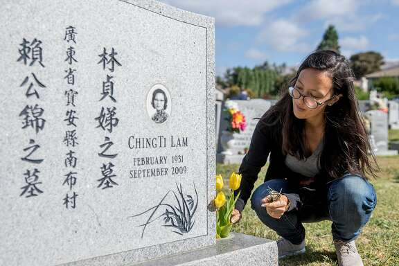 Writer Janelle Bitker cleans off a gravestone while she participates in a Chinese tomb sweeping holiday for Janelle's late grandmother Ching Ti Lam and late grandfather Kam Lai at Cedar Lawn Cemetery in Fremont, Calif. Saturday, Sept. 28, 2019.