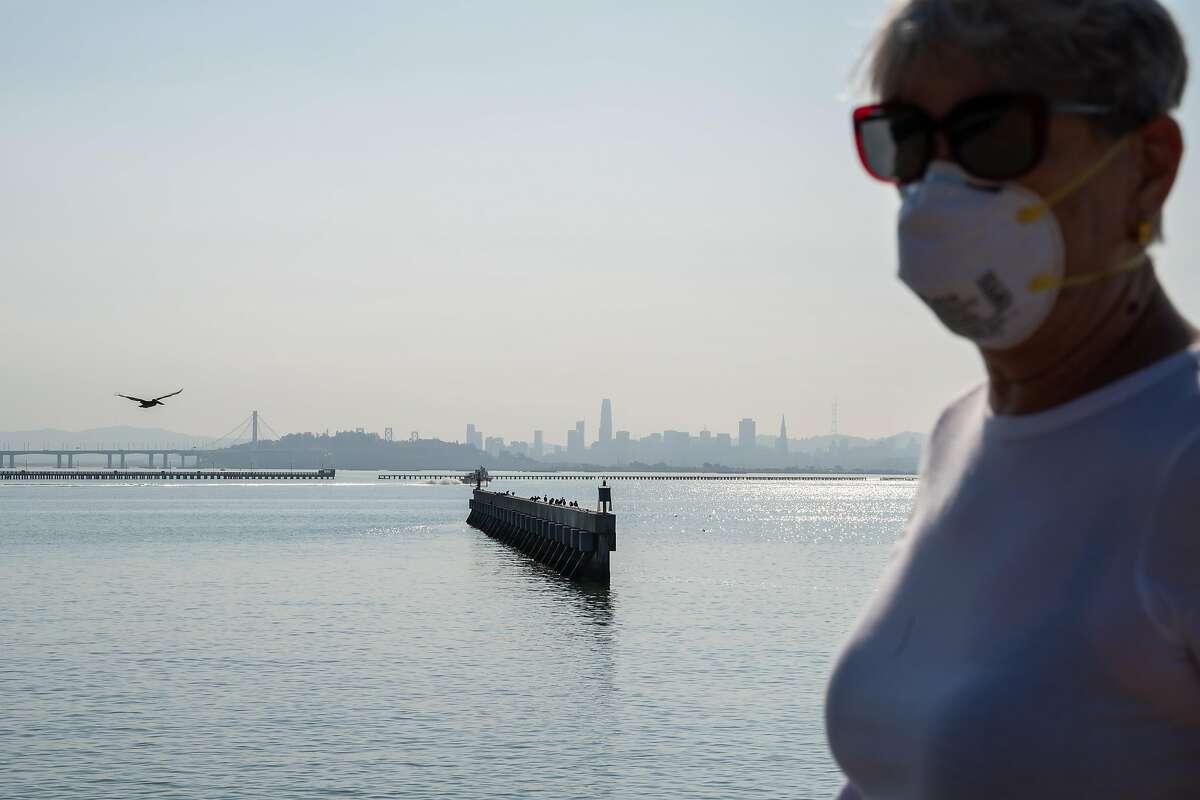 Sara Orem of Berkeley, walks at the marina wearing an N95 mask in Berkeley, Calif. on Monday, Oct. 28, 2019.