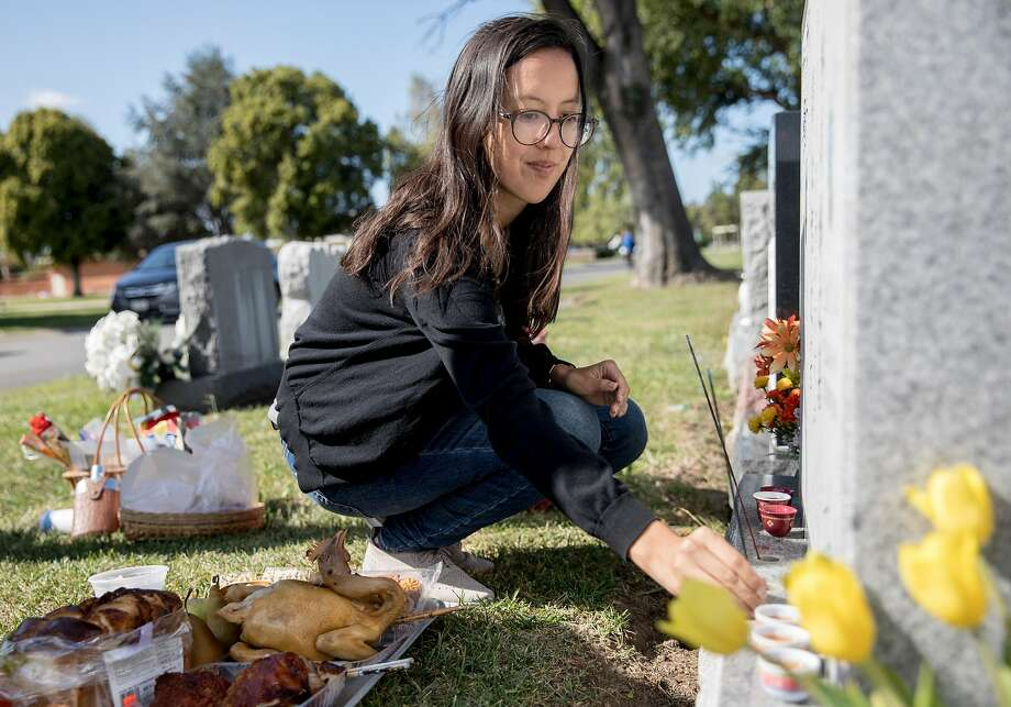 Chronicle reporter Janelle Bitker places incense on the gravestone of her grandparents. Photo: Jessica Christian / The Chronicle