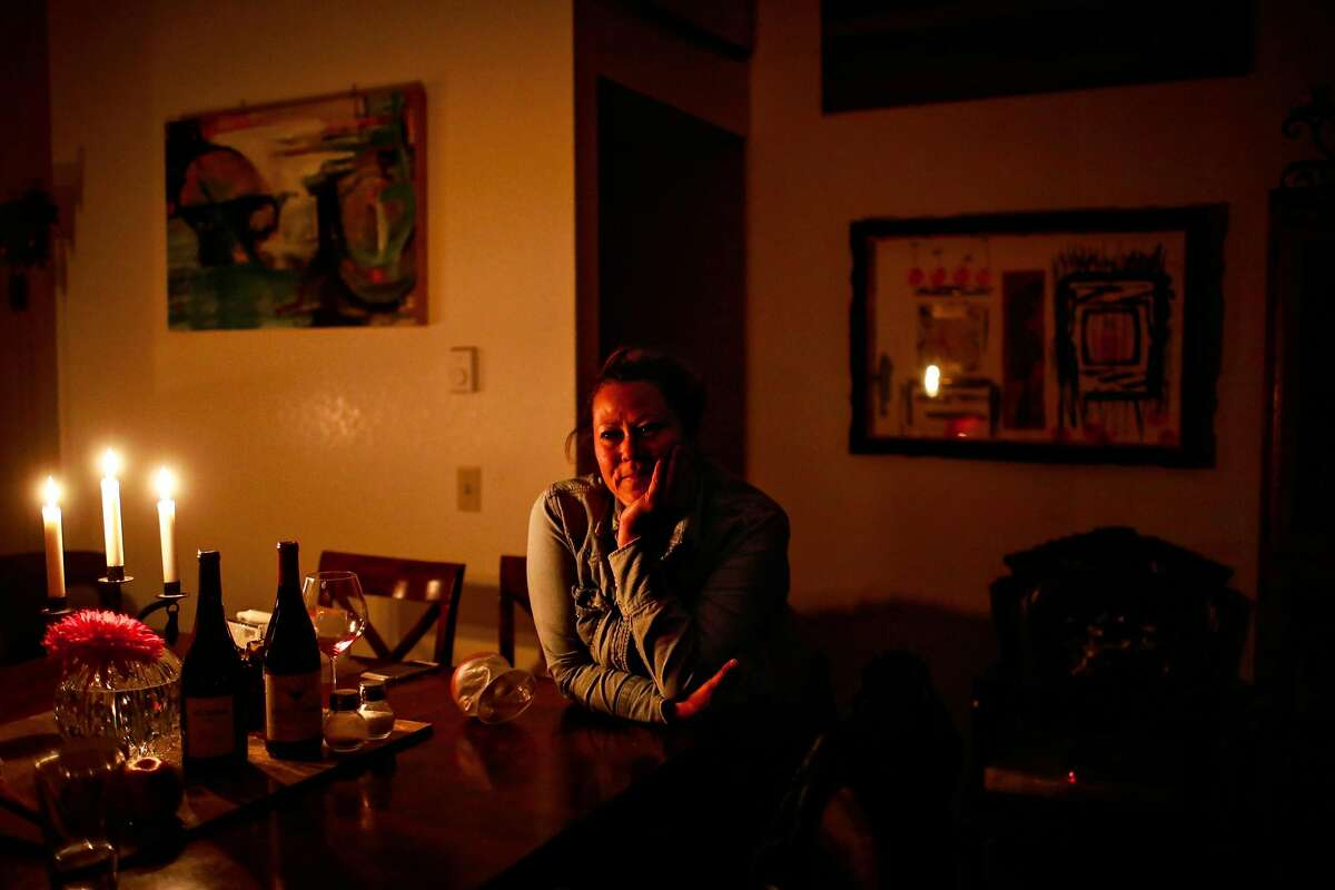 Wanda Brester, owner of L&M motel sits at her dining room table lit by candles because she has no power following the Kincade Fire in Healdsburg, California, on Monday, Oct. 28, 2019.