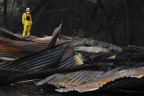 Cal Fire Damage Inspection crewmember Carlos Hernandez assesses the damage to a destroyed woodshop along Highway 128 in Healdsburg, Calif, Tuesday, October 10, 2019 after a handful of buildings were destroyed on Hank Wetzel�s peoperty by the Kincade Fire.