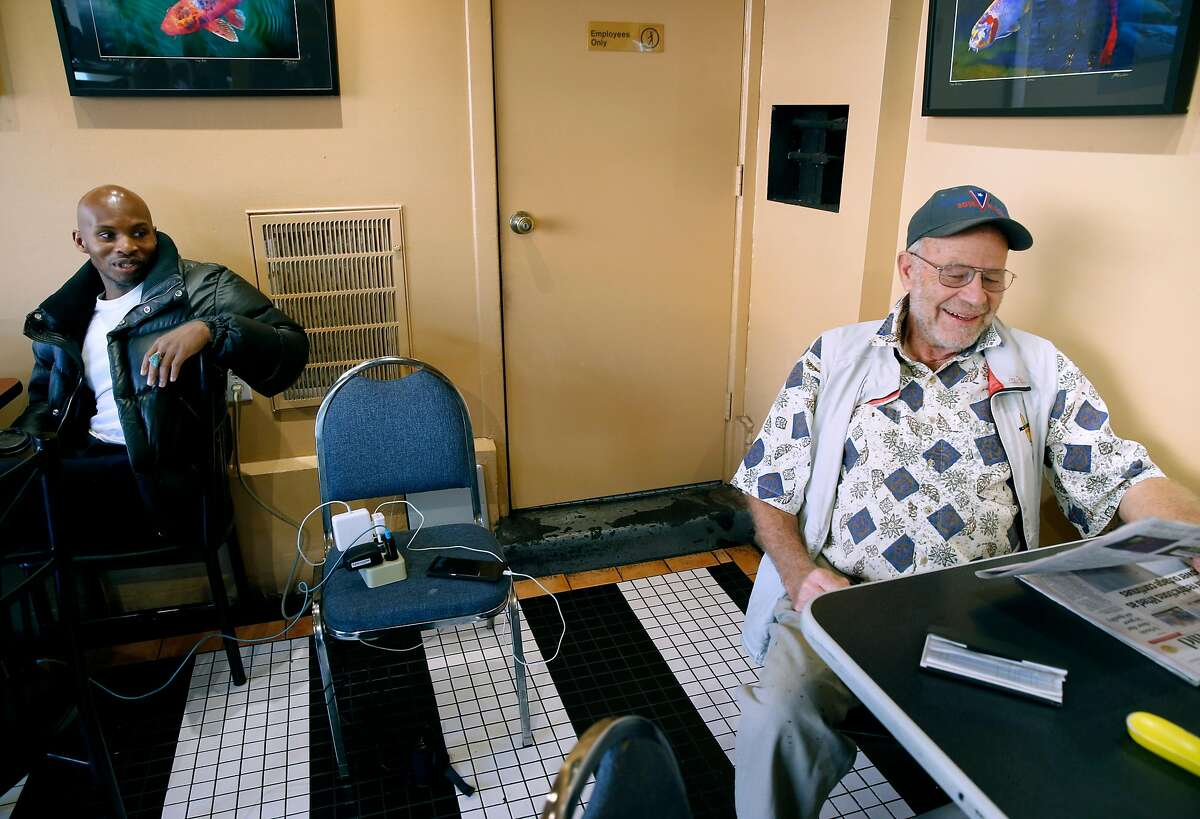 Fox Scott (left) and Robert Boyce recharge their mobile devices at Java Jax on Sonoma Boulevard, one of the few businesses still with electricity, as the public safety power shutoff issued by PG&E continues for a third consecutive day in Vallejo, Calif. on Tuesday, Oct. 29, 2019.