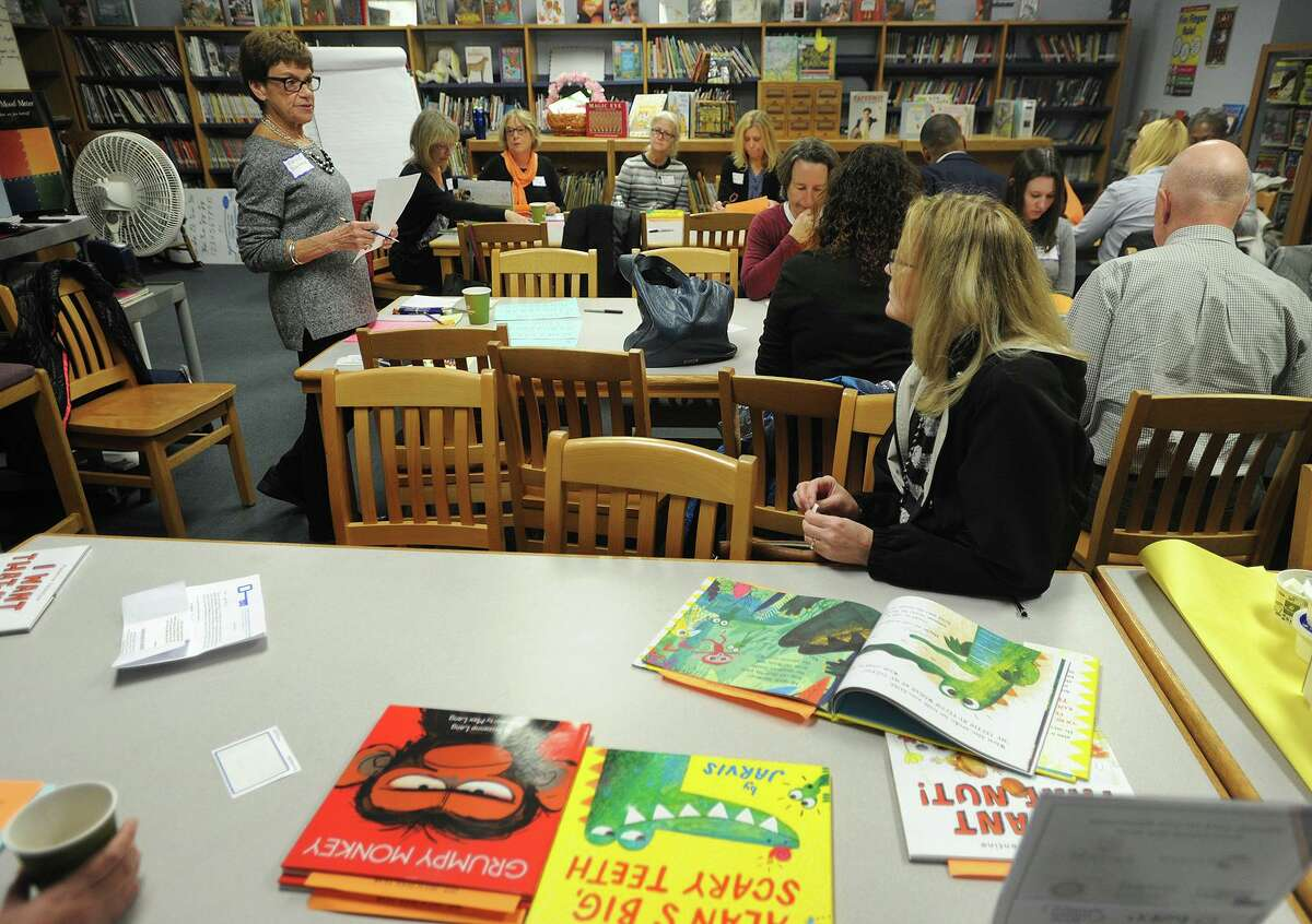 Volunteer readers gather in the library of Bryant School in Bridgeport before heading off to classrooms for the 33rd Annual Read Aloud Day in Bridgeport, Conn. on Thursday, October 18, 2018. Over six hundred readers spread out to read to to every pre-kindergarten to sixth grade class in the Bridgeport Public Schools.