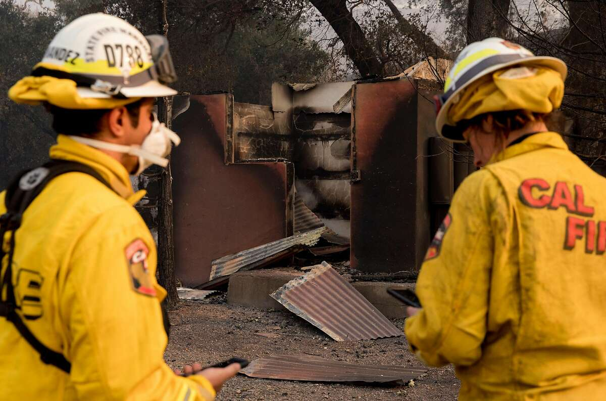 This file photograph shows Cal Fire Damage Inspection crew members Carlos Hernandez (left) and Kim Sone input information into their Collector app used to record structure damage as they assess a property for damage along Highway 128 in Healdsburg, Calif. Tuesday, Oct. 29, 2019 after the Kincade Fire ripped through Alexander Valley.
