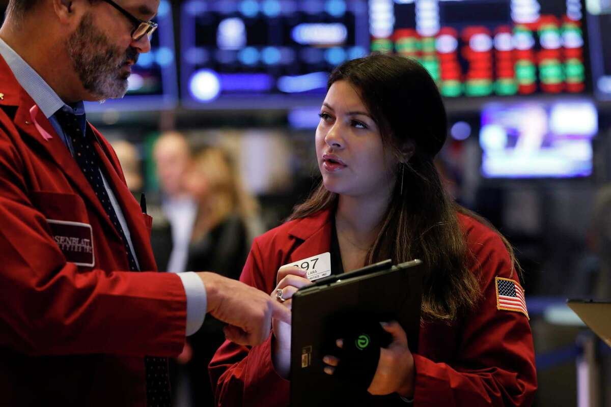 Traders William Lawrence, center, and Ashley Lara work on the floor of the New York Stock Exchange, Tuesday, Oct. 29, 2019.
