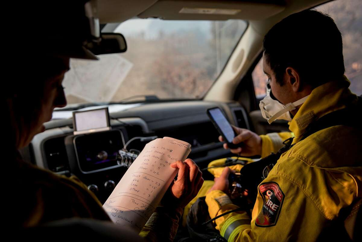 Cal Fire Damage Inspection crew members Kim Sone (left) and Carlos Hernandez look at the latest fire numbers and input information into their Collector app used to record structure damage as they assess residential properties or damage along Highway 128 in Healdsburg, Calif. Tuesday, Oct. 29, 2019 after the Kincade Fire ripped through Alexander Valley.