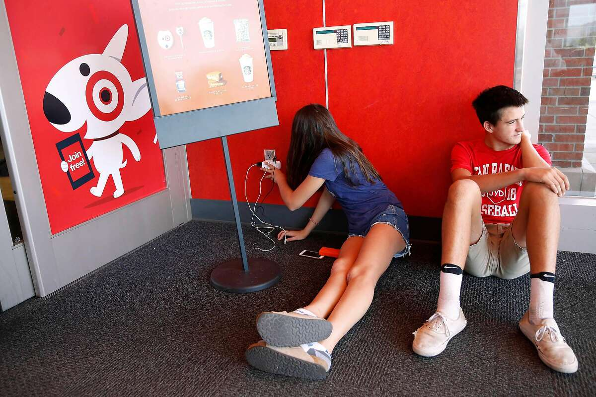 Siblings Mary Healy, 14, (l to r) and Jack Healy, 15, both of San Rafael sit next to an outlet at Target as they charge their devices on Tuesday, October 29, 2019 in San Rafael, Calif.