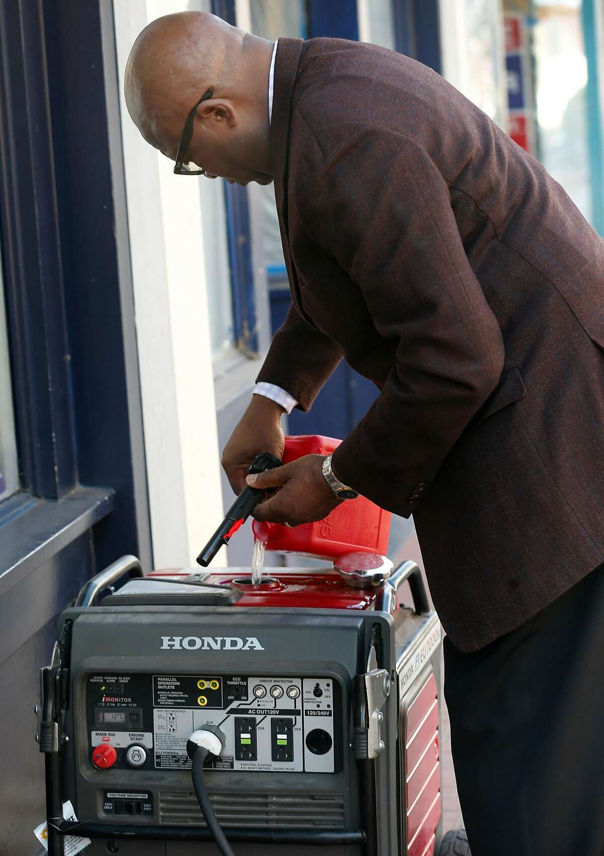 Capital City Pharmacy owner Arthur Metu fills a rented portable generator with gasoline on Georgia Street as the public safety power shutoff issued by PG&E continues for a third consecutive day in Vallejo, Calif. on Tuesday, Oct. 29, 2019. Metu had to drive all the way to Livermore to pick up the generator, the closest location he could find.