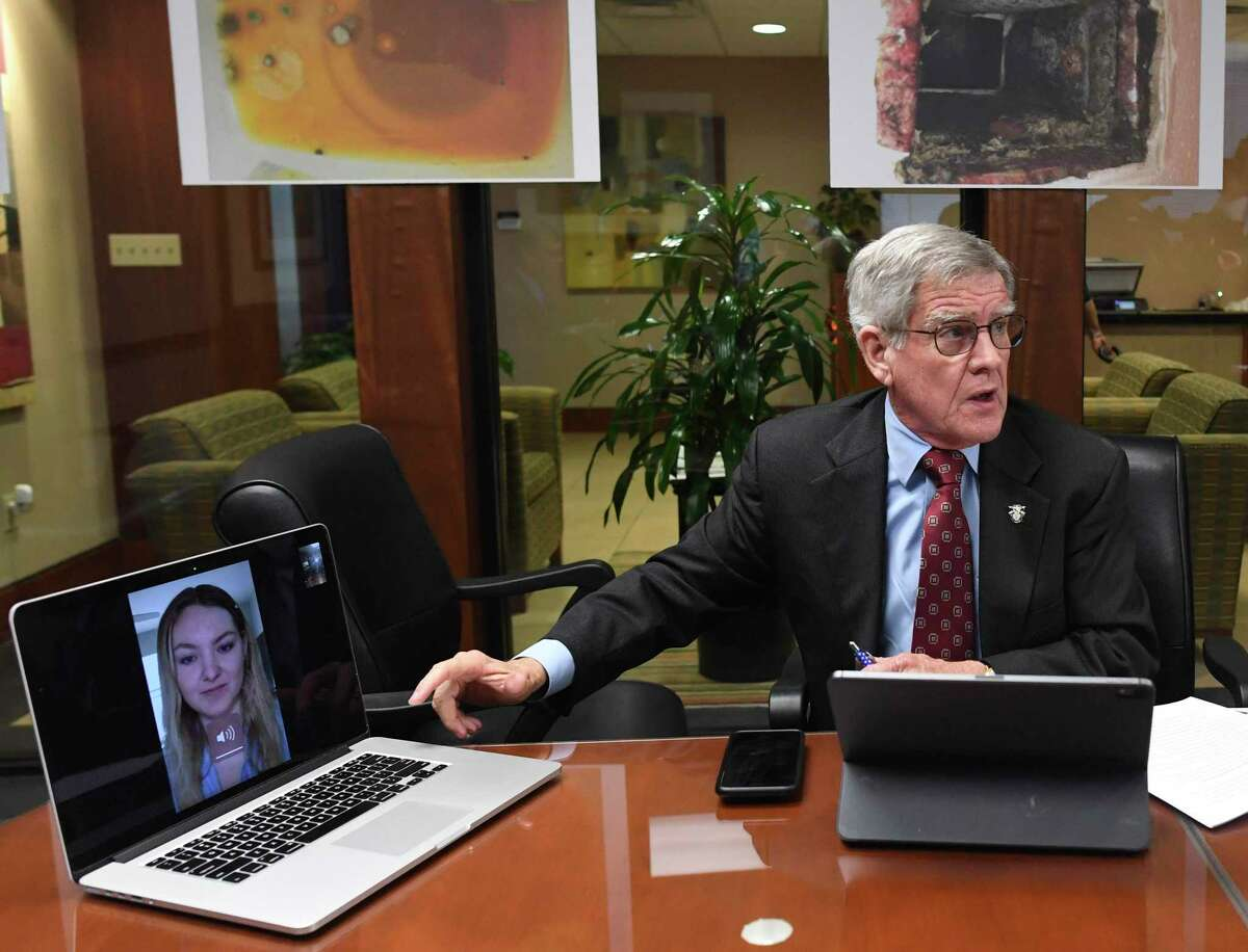 Attorney James R. Moriarty speaks with Megan Konzen, onscreen, whose husband is a pilot in the Air Force, during a press conference Tuesday at the Pulman, Cappuccio and Pullen law firm office about a lawsuit against a private housing contractor over problems with mold and other issues at Joint Base San Antonio-Randolph and Laughlin AFB near Del Rio.