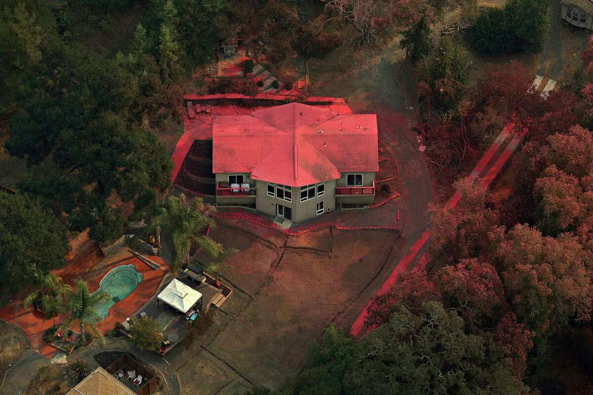 A Healdsburg, Calif., home is covered in fire retardant as a wildfire called the Kincade Fire burns in Sonoma County on Tuesday, Oct. 29, 2019. (Guy Wathen/San Francisco Chronicle via AP)