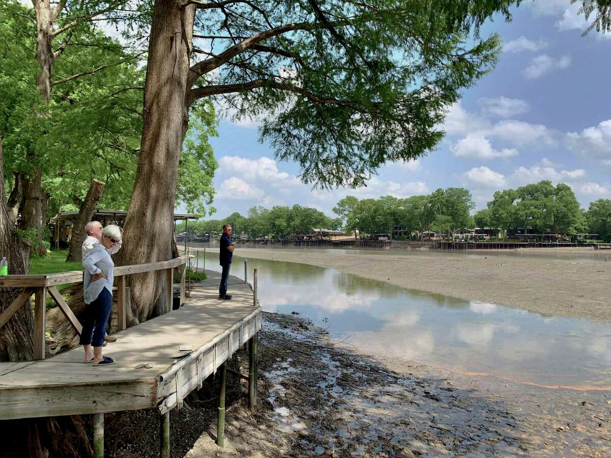 People look at the receding water of Lake Dunlap on May 15, the day after a spill gate collapsed, draining much of the water.