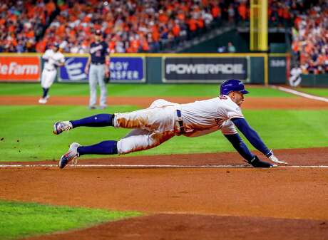 Houston Astros center fielder George Springer (4) slides into home plate on a sacrifice fly hit by Houston Astros second baseman Jose Altuve (27) to tie the game 1-1 during the first inning of Game 6 of the World Series at Minute Maid Park on Tuesday, Oct. 29, 2019, in Houston.